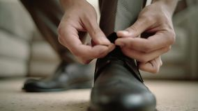 Το παπούτσι επιχειρησιακών ατόμων που δένουν τις δαντέλλες στο νεόνυμφο πατωμάτων φορά τα μαύρα παπούτσια στην κινηματογράφηση σε απόθεμα βίντεο