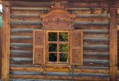 Το παράθυρο με τον ξύλινο που χαράζεται architrave στο παλαιό ξύλινο σπίτι στην παλαιά ρωσική πόλη Στοκ Εικόνα
