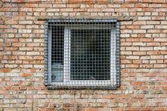 Το παράθυρο πίσω από τη σχάρα σιδήρου σε έναν τουβλότοιχο Στοκ Εικόνα