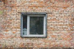 Το παράθυρο πίσω από τη σχάρα σιδήρου σε έναν τουβλότοιχο Στοκ εικόνες με δικαίωμα ελεύθερης χρήσης