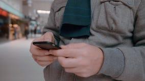 Το παραγνωρισμένο άτομο με ένα γαμήλιο δαχτυλίδι χρησιμοποιεί ένα smartphone Σε αργή κίνηση κινηματογράφηση σε πρώτο πλάνο φιλμ μικρού μήκους