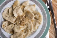 Το παραδοσιακές ουκρανικές ή ρωσικές vareniki ή οι μπουλέττες γεύματος με την πατάτα εξυπηρέτησε με το καραμελοποιημένο αλατισμέν στοκ φωτογραφίες