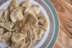 Το παραδοσιακές ουκρανικές ή ρωσικές vareniki ή οι μπουλέττες γεύματος με την πατάτα εξυπηρέτησε με το καραμελοποιημένο αλατισμέν στοκ φωτογραφία με δικαίωμα ελεύθερης χρήσης