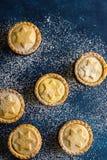 Το παραδοσιακό βρετανικό σπίτι ζύμης Χριστουγέννων που ψήνεται κομματιάζει τις πίτες με την πλήρωση καρυδιών σταφίδων της Apple π Στοκ Φωτογραφία