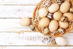 Το παραδοσιακό πρότυπο καρτών Πάσχας με τα χρώματα κρητιδογραφιών χρωμάτισε τα οργανικά αυγά στο ψάθινο καλάθι με το σανό και τα  Στοκ φωτογραφία με δικαίωμα ελεύθερης χρήσης