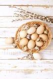 Το παραδοσιακό πρότυπο καρτών Πάσχας με τα χρώματα κρητιδογραφιών χρωμάτισε τα οργανικά αυγά στο ψάθινο καλάθι με το σανό και τα  Στοκ Εικόνα