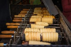 Το παραδοσιακό τσεχικό γλυκό μεταχειρίζεται Trdelnik στα ειδικά ξύλινα οβελίδια πέρα από τους καυτούς άνθρακες Στοκ εικόνες με δικαίωμα ελεύθερης χρήσης