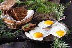 Το παραδοσιακό υγιές εύκολο γρήγορο γεύμα προγευμάτων φιαγμένο από δύο τηγανισμένα αυγά εξυπηρέτησε σε ένα τηγανίζοντας τηγάνι Στοκ Εικόνες