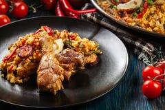 Το παραδοσιακό paella με τα πόδια κοτόπουλου, chorizo λουκάνικων και τα λαχανικά εξυπηρέτησε στο μαύρο πιάτο Στοκ φωτογραφία με δικαίωμα ελεύθερης χρήσης