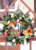 Το παραδοσιακό στεφάνι Χριστουγέννων με τους πράσινους κλαδίσκους δέντρων έλατου και τις κόκκινες σφαίρες κρεμά σε ένα wicket Στοκ Φωτογραφίες