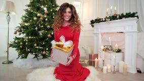 Το παρόν για τη Παραμονή Πρωτοχρονιάς, το κορίτσι δίνει ένα δώρο, πορτρέτο, κόμμα, όμορφη νέα γυναίκα στο φόρεμα βραδιού που έχει απόθεμα βίντεο