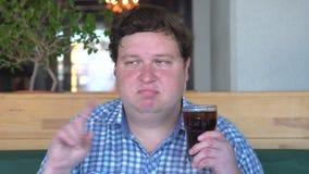 Το παχύ άτομο κρατά ότι ένα γυαλί πίνει την κόλα στον καφέ και το ρητό του αριθ. με το τίναγμα του κεφαλιού απόθεμα βίντεο