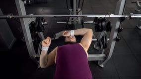 Το παχύ άτομο σκουπίζει το μέτωπο, που κουράζεται μετά από να ανυψώσει barbell επάνω, εξαντλώντας workouts στοκ φωτογραφία με δικαίωμα ελεύθερης χρήσης