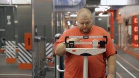 Το παχύ άτομο στέκεται και χρησιμοποιεί τις παλαιές κλίμακες για τη μέτρηση βάρους απόθεμα βίντεο