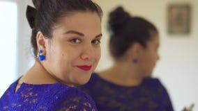 Το παχύ κορίτσι χρωματίζει τα χείλια της μπροστά από έναν καθρέφτη απόθεμα βίντεο