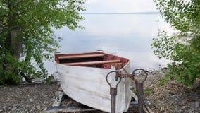 Το παλαιό αλιευτικό σκάφος κωπηλασίας είναι δεμένο και αβοήθητο με την αλυσίδα στην ακτή ποταμών απόθεμα βίντεο