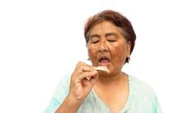 Το παλαιό γκρίζο ανοικτό στόμα γυναικών και προετοιμάζεται να βάλει μια οδοντοστοιχία (απομονωμένο υπόβαθρο) στοκ εικόνες