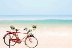 Το παλαιό κόκκινο ποδήλατο με τα λουλούδια καλαθιών επάνω η τροπική θάλασσα παραλιών Στοκ φωτογραφία με δικαίωμα ελεύθερης χρήσης