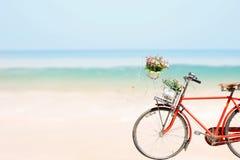 Το παλαιό κόκκινο ποδήλατο με τα λουλούδια καλαθιών επάνω η τροπική θάλασσα παραλιών Στοκ Εικόνα