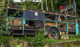 Το παλαιό, μετα αποκαλυπτικό κοίταγμα αποσυντέθηκε και να σαπίσει λεωφορείο στα ξύλα Στοκ φωτογραφία με δικαίωμα ελεύθερης χρήσης