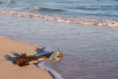 Το παλαιό μπουκάλι βάζει στην παραλία με την κίνηση θαλασσίων φυτών και κυμάτων μέσα Στοκ εικόνα με δικαίωμα ελεύθερης χρήσης