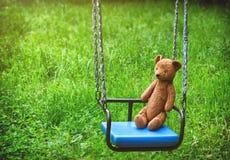 Το παλαιό παιχνίδι teddy αφορά την μπλε πλαστική ταλάντευση Στοκ Εικόνα