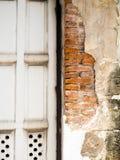 Το παλαιό σπασμένο τοίχος τούβλο βλέπει έναν πορτοκαλή brickwall μέσα Η πλευρά έχει τις παλαιές γκρίζες ξύλινες πόρτες Στοκ Φωτογραφίες
