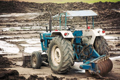 Το παλαιό τρακτέρ στην κατασκευή ρυθμίζει το έδαφος Στοκ Εικόνες