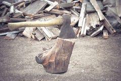 Το παλαιό τσεκούρι είναι κολλημένο σε μια παλαιά σύνδεση το υπόβαθρο του ξύλινου καυσόξυλου που βρίσκεται στο έδαφος Στοκ Εικόνες