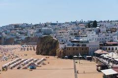 Το παλαιό albufeira κωμοπόλεων της Πορτογαλίας Αλγκάρβε και οι αμμώδεις άνθρωποι παραλιών πόλεων κάνουν ηλιοθεραπεία και στηρίζον Στοκ Εικόνα