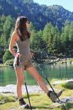 Το πεζοποριες κορίτσι εξετάζει την πράσινη λίμνη βουνών Στοκ Εικόνες