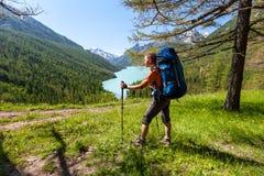 Το πεζοπορώ γυναικών με το σακίδιο πλάτης στη λίμνη των ορεινών περιοχών Altai τοποθετεί Στοκ Εικόνα