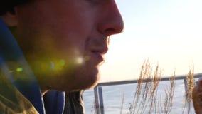 Το πεινασμένο άτομο μασά στη φύση ένα χάμπουργκερ στον ήλιο με μια επίδραση φακών 3840x2160, 4K απόθεμα βίντεο