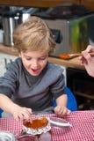 Το πεινασμένο αγόρι βυθίζει ένα δάχτυλο σε ένα βάζο της μαρμελάδας Στοκ Φωτογραφίες