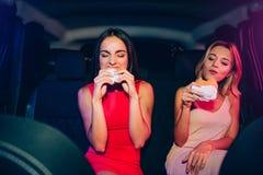 Το πεινασμένο κορίτσι τρώει τα burgers τους Συγκεντρώνονται πολύ σε αυτήν την διαδικασία Το κορίτσι Brunette δαγκώνει burger Ξανθ Στοκ Φωτογραφία