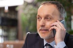 Το πεπειραμένο παλαιό senor χρησιμοποιεί το τηλέφωνο στον καφέ Στοκ φωτογραφία με δικαίωμα ελεύθερης χρήσης