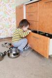 Το περίεργο μωρό εξετάζει το συρτάρι στην κουζίνα Στοκ Εικόνα