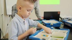 Το περίεργο ξανθό καυκάσιο παιδί δοκιμάζει πώς να κατασκευάσει το πλαστικό παιχνίδι ρομπότ στην κατηγορία σε αργή κίνηση φιλμ μικρού μήκους