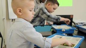 Το περίεργο ξανθό καυκάσιο παιδί δοκιμάζει πώς να κατασκευάσει το πλαστικό παιχνίδι ρομπότ στην κατηγορία σε αργή κίνηση απόθεμα βίντεο