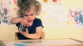 Το περίεργο παιδί μικρών παιδιών χύνει το νερό στον πίνακα Συγκινημένο υγρό παιχνίδι παιδιών με το νερό απόθεμα βίντεο