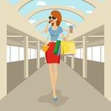 Το περπάτημα γυναικών μόδας με τις αγορές τοποθετεί την ομιλία στο τηλέφωνο στη λεωφόρο αγορών σε σάκκο Στοκ Φωτογραφία