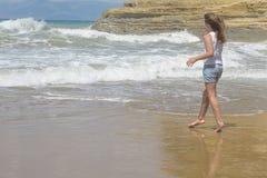 Το περπάτημα κοριτσιών και κοιτάζει στα κύματα θάλασσας Στοκ εικόνες με δικαίωμα ελεύθερης χρήσης