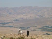 Το περπατώντας άτομο που βλέπει από πίσω με στην πλευρά του άλλης μιας σε ένα άσπρο άλογο στα βουνά της Τουρκίας στοκ εικόνες