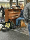 Το πιάνο busker αποδίδει στη βροχερή οδό της Αμβέρσας, Βέλγιο στοκ εικόνα με δικαίωμα ελεύθερης χρήσης