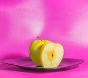 Το πιάτο η κίτρινη Apple σε ένα ρόδινο υπόβαθρο Στοκ Φωτογραφία