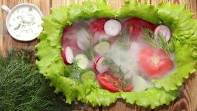 Το πιάτο με το μαρούλι, τις τεμαχισμένες ντομάτες, το αγγούρι και το ραδίκι με τον άνηθο, εξυπηρέτησε την ομίχλη πρωινού Ένας ασθ απόθεμα βίντεο