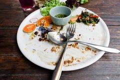 Το πιάτο με τα απορρίματα τροφίμων και η σάλτσα μετά από τρώνε τα ταϊλανδικά τρόφιμα στοκ εικόνες
