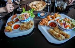 Το πιάτο του τηγανισμένου ρόλου άνοιξη, fritters γαρίδων, τσιγάρισε τις σουπιές καλαμαριών και τηγάνισε wonton Στοκ εικόνα με δικαίωμα ελεύθερης χρήσης