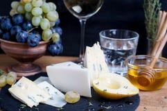 Το πιάτο τυριών εξυπηρέτησε με το κρασί, τα σταφύλια, το μέλι και το αχλάδι σε ένα σκοτάδι στοκ εικόνα με δικαίωμα ελεύθερης χρήσης