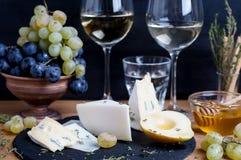 Το πιάτο τυριών εξυπηρέτησε με το κρασί, τα σταφύλια, το μέλι και το αχλάδι σε ένα σκοτάδι στοκ φωτογραφίες